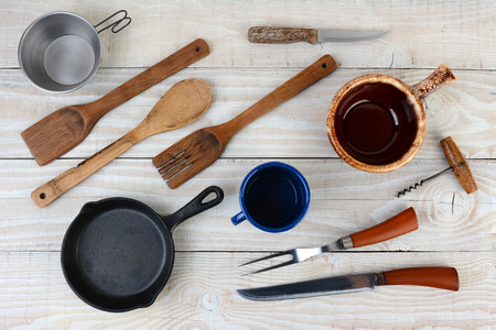 cork screw: High angle shot of assorted kitchen and camping utensils. Items include: pan, bowl, cup, knife, fork, cork screw. Horizontal format.