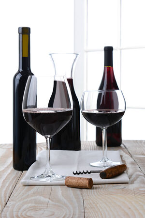 High key wine still life. Vertical format on a farmhouse style table with a white background with window panes. Shallow depth of field.