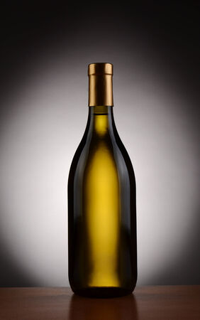 chardonnay: Chardonnay  wine bottle over a spot light to dark background. Bottle is without a label in vertical format. Stock Photo