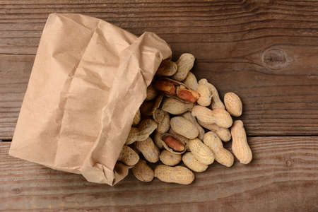 ballgame: HIgh angle view of peanuts spilling from brown paper bag, Horizontal format on a wood background. Stock Photo