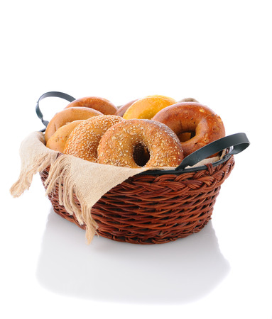 A basket of assorted bagels on a white surface with reflection. A variety of bagels including: egg, sesame, multi-grain, onion, and cinnamon.