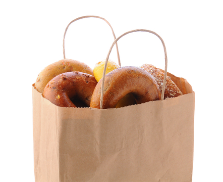 bagel: Closeup of a brown paper bag filled with a variety of different bagels. Bagels include: onion, blueberry, egg and multi-grain. Horizontal format isolated on white.
