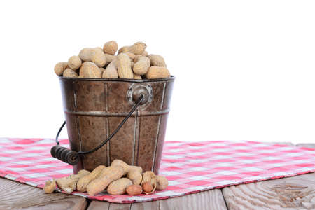 Closeup of a pail full of peanuts on a wood picnic table and a red checked tablecloth. Horizontal format with a white background.