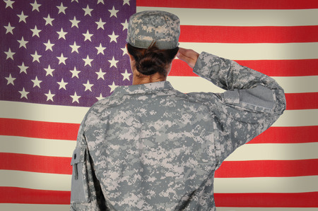 Female Soldier standing in front of and saluting an American flag. Woman is seen form behind only showing her from the waist up. Horizontal format. Stockfoto