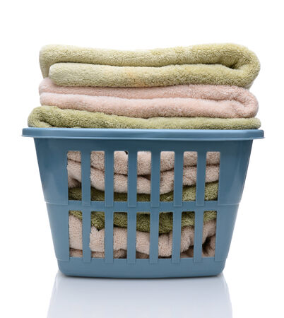 laundry basket: Closeup of a laundry basket filled with folded towels. The blue plastic basket is isolated on white with reflection.