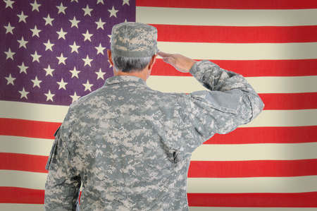 salute: Closeup of a middle aged American soldier in fatigues saluting an old and weathered flag. The flag fills the frame and is out of focus. Man is seen from behind. Stock Photo