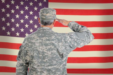 tercera edad: Primer plano de un soldado americano de mediana edad en traje de faena que saludan un viejo y degradado bandera. La bandera llena el cuadro y est� desenfocada. El hombre es visto desde atr�s.