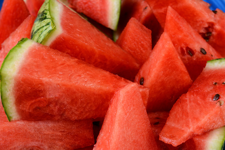 Closeup of a plate full of watermelon slices and wedges. Horizontal format filling the frame. photo