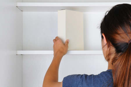 hands behind head: Closeup of a young woman reaching into a cupboard to get the only box of food from the empty shelves. Seen from behind the focus is on the box and hand. Stock Photo