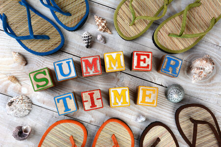 Childrens Blocks Spelling Out Summer Time on a rustic wooden boardwalk. The words are surrounded buy sea shells and flip-flop style sandals. Horizontal format.