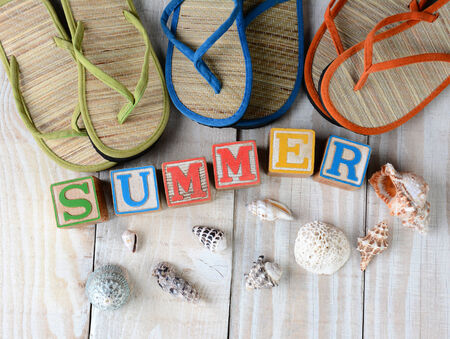 Childrens blocks spelling out Summer on rustic wooden boards The word is surrounded by sea shells, and flip-flop style sandals. Horizontal format. photo
