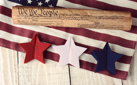 high angle shot: A rolled up US Constitution on an American Flag with red white and blue stars in the foreground. High angle shot on a rustic wooden table. The image has a vintage retro feel. Great for Independence Day projects.