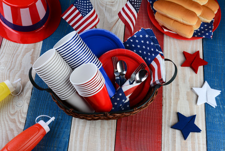 High angle photo of a picnic table ready for Fourth of July Party. The red white and blue table is set with plates, cups, hot dog buns, cups, forks, Uncle Sam Hat, Ketchup and Mustard dispensers.
