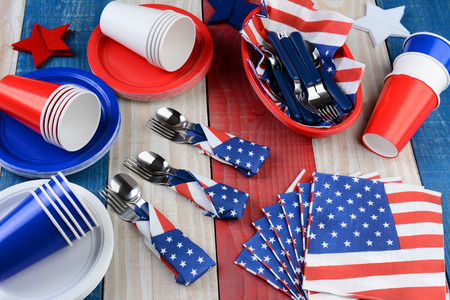high day: High angle photo of a picnic table setting for a Fourth of July party. Plates, cups, napkins, and other items in patriotic red, white and blue. Horizontal format. Stock Photo