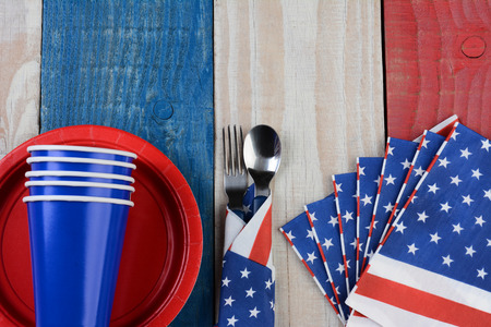 High angle photo of a Fourth of July picnic table setting. The red white and blue items are on a wood table painted for the holiday. photo