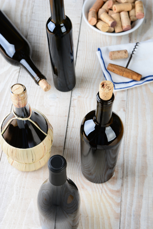 Wine still life shot from a high angle. Five bottles of wine with a cork screw napkin and bowl of corks on a rustic farmhouse style table. Vertical format. photo