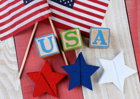 A patriotic display of American Flags, red, white and blue stars and USA spelled out with alphabet blocks on a red and white wood . High angle shot in horizontal format. photo