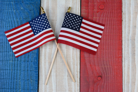 fourth of july: Two American Flags on a red, white and blue painted wood surface. Perfect for Fourth of July or Memorial Day projects. Stock Photo