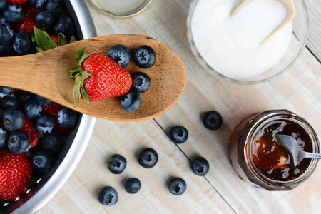 High angel photo of a Strawberry and Blueberries on a wooden spoon laying across a colander full of berries. A sugar bowl and jar of jam sitting on a rustic wooden farmhouse style table fill the background. Selective focus in horizontal format. photo
