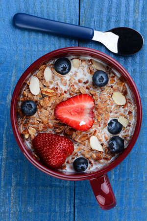 High angle photo of a large mug filled with a healthy whole grain cereal and fruit. Strawberries, blueberries and sliced almonds on a rustic painted kitchen table. Vertical format but works as a horizontal also. photo