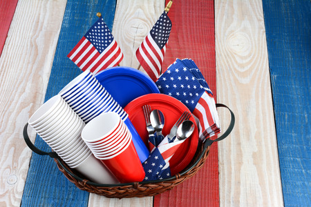 High angle photo of a picnic table ready for Fourth of July Party. A Basket full of Cups, plates, utensils, napkins and American Flags sits in the middle of the red white and blue table. photo