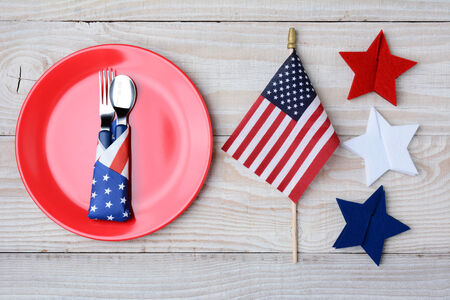 A picnic table ready for a 4th of July picnic. A red plate with fork and spoon, American Flag and felt stars decorate the table. photo