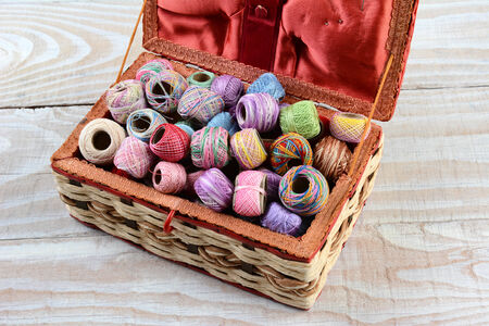 basket embroidery: High angle shot of a sewing box filled with thread. A variety of embroidery threads in a wicker basket on a rustic wooden table. Stock Photo