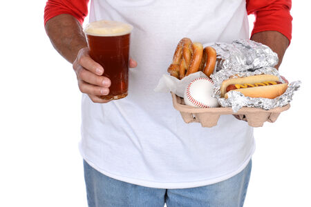 Closeup of a sports fan carrying a tray of food and souvenirs in one hand and a beer in the other. Food tray holds hot dogs and pretzels and a souvenir baseball. photo