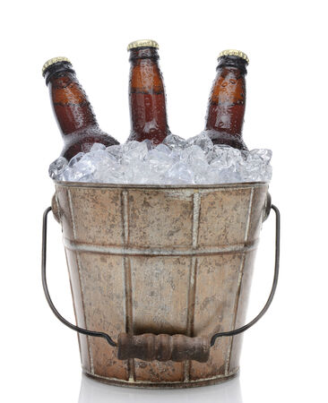 Closeup of an old fashioned beer bucket with three brown bottles of cold beer. Isolated on white with reflection. photo