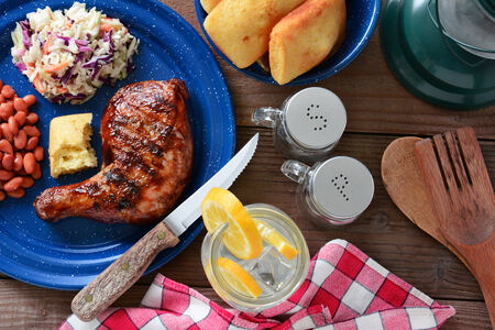 High angle shot of a barbecue chicken plate with cole slaw, pinto beans and corn bread. The meal is on a rustic wooden restaurant table with a red and white checked napkin and a glass of lemonade. photo