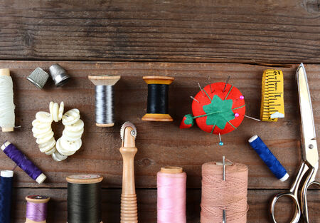 implements: High angle shot of antique sewing tools on a rustic wooden surface. Items include, Thread, scissors, pin cushion, buttons, thimble, tape measure and more.