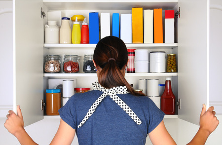 A woman seen from behind opening the doors to a fully stocked pantry. The cupboard is filled with various food stuff and groceries all with blank labels. Horizontal format, the woman is unrecognizable.
