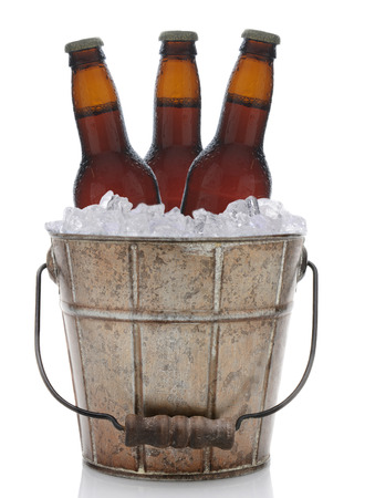 An old fashioned bucket filled with ice and beer bottles. Three brown bottles of beer are represented in vertical format on a white with reflection. photo