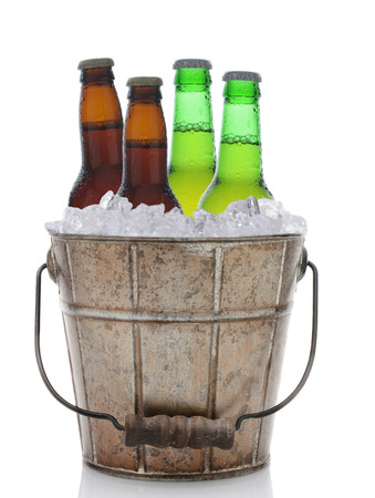 An old fashioned bucket filled with ice and beer bottles. Four brown and green bottles of beer are represented in vertical format on a white with reflection.