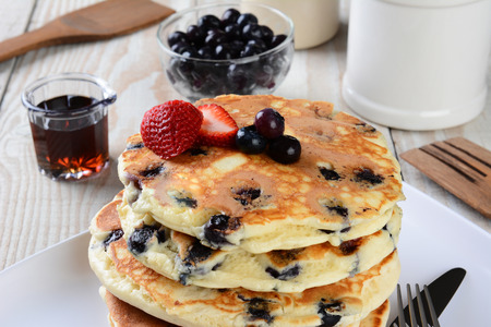 Blueberry Pancake Closeup with syrup pitcher, wooden spatula and fork, blueberry bowl and other items set out for a homemade breakfast. Horizontal format. photo