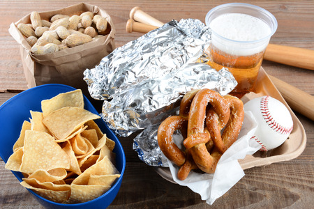 Closeup of a tray of food and souvenirs that one would find at a baseball game. Items include, hot dogs wrapped in foil, beer, peanuts, chips, baseball, mini bats and pretzels. Horizontal format. Stock Photo