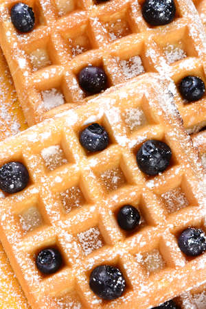 High angle shot of blueberry waffles. Closeup of waffles covered with powdered sugar and fresh blueberries.