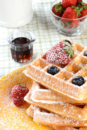 Waffles with strawberries and blueberries covered with powdered sugar. Vertical format with syrup and a bowl of fresh strawberries and a crock. photo
