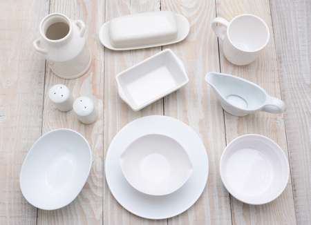 High angle shot of different dinnerware items,  of varying shades of white.  Horizontal format on a rustic whitewashed farmhouse style kitchen table. photo