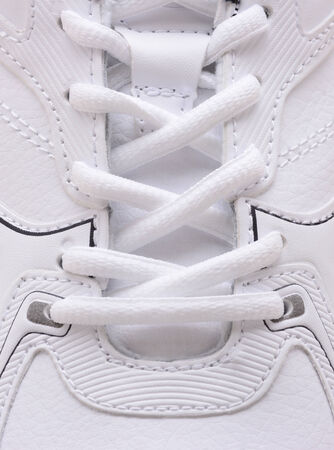 sneaks: Closeup of the laces on a brand new sneaker. The athletic shoe is all white as are the laces filling the vertical frame.  Stock Photo