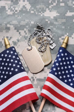 Closeup of two crossed American Flags on camouflage material with dog tags in the middle. The ID tags are blank. Vertical format filling the frame.