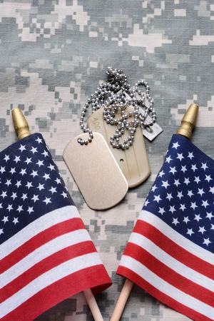Gros plan de deux drapeaux croisés américains sur le matériel de camouflage avec des étiquettes de chien dans le milieu. Les étiquettes d'identification sont vides. Format vertical remplissant le cadre. Banque d'images - 29126898