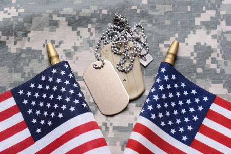 2 つのクローズ アップ途中で犬のタグを camouflage マテリアルにアメリカ国旗を渡った。ID タグは空白です。水平形式フレームを充填します。 写真素材