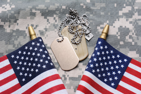 military uniform: Closeup of two crossed American Flags on camouflage material with dog tags in the middle. The ID tags are blank. Horizontal format filling the frame.
