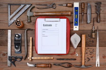 High angle shot of a contractors estimate form surrounded by his well used tools. Horizontal format on a rustic wood background. photo