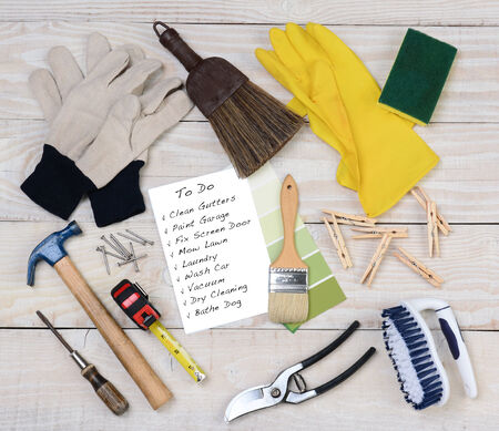 A Honey-Do List surrounded by the tools necessary to do the jobs. Itms include: hammer, nails, paint brush, gloves, rubber gloves, scrub brush, paint chips, clothes pins, pruning shears. Square format on rustic wood background.