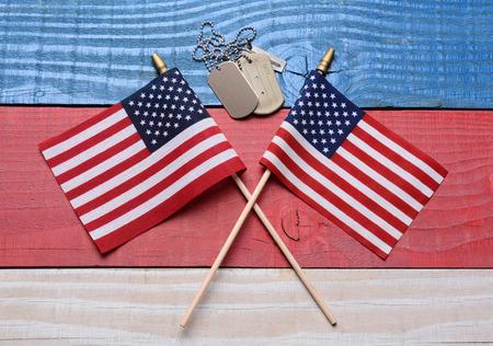 두 군사 강아지 태그와 함께, 흰색 빨간색과 파란색 나무 테이블에 미국 국기를 건넜다. 월, 현충일, 재향 군인의 날이나 군사 프로젝트의 4 일을위한