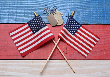 Two crossed American flags on a red, white and blue wood table with military dog tags. Great concept image for the 4th of July, Memorial Day,  Veterans Day or military projects. photo