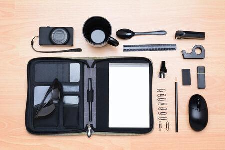 office stapler: High angle shot of all black assorted desk items. Items include: mug, stapler, pencil, pen, eraser, paper clips, notebook, mouse, sunglasses, spoon, tape dispenser, camera and ruler. Stock Photo