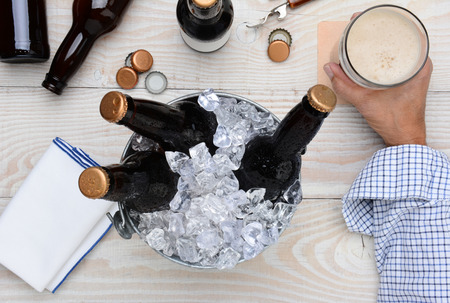 High angle shot of a man holding a glass of beer with a metal bucket with unopened bottles. The rustic wood table has empty bottles and caps and an bottle opener.  photo